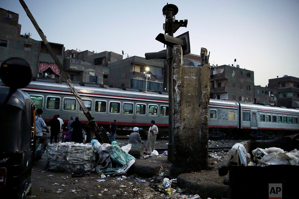 In this Oct. 23, 2018 photo, people wait for the train to pass in Shubra, Cairo, Egypt. (AP Photo/Nariman El-Mofty)