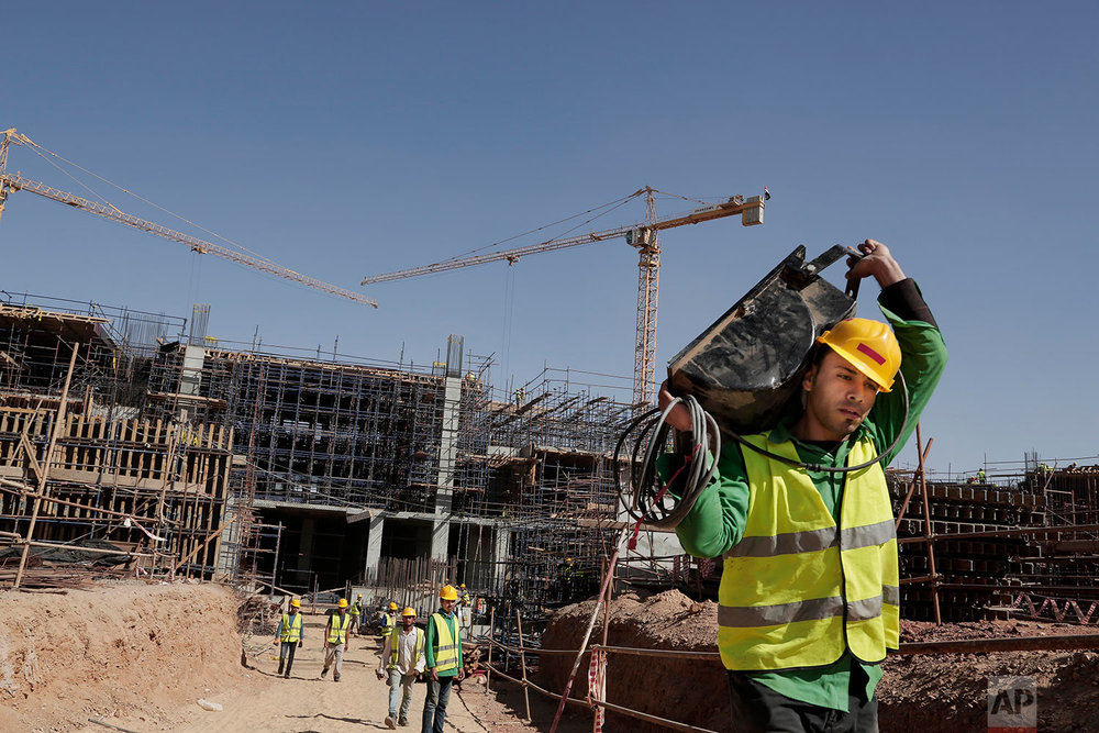 In this Oct. 18, 2017 photo, laborers build the ministers cabinets and parliament at a construction site in the New Administrative Capital, 45 kilometers (28 miles) east of Cairo, Egypt. (AP Photo/Nariman El-Mofty)