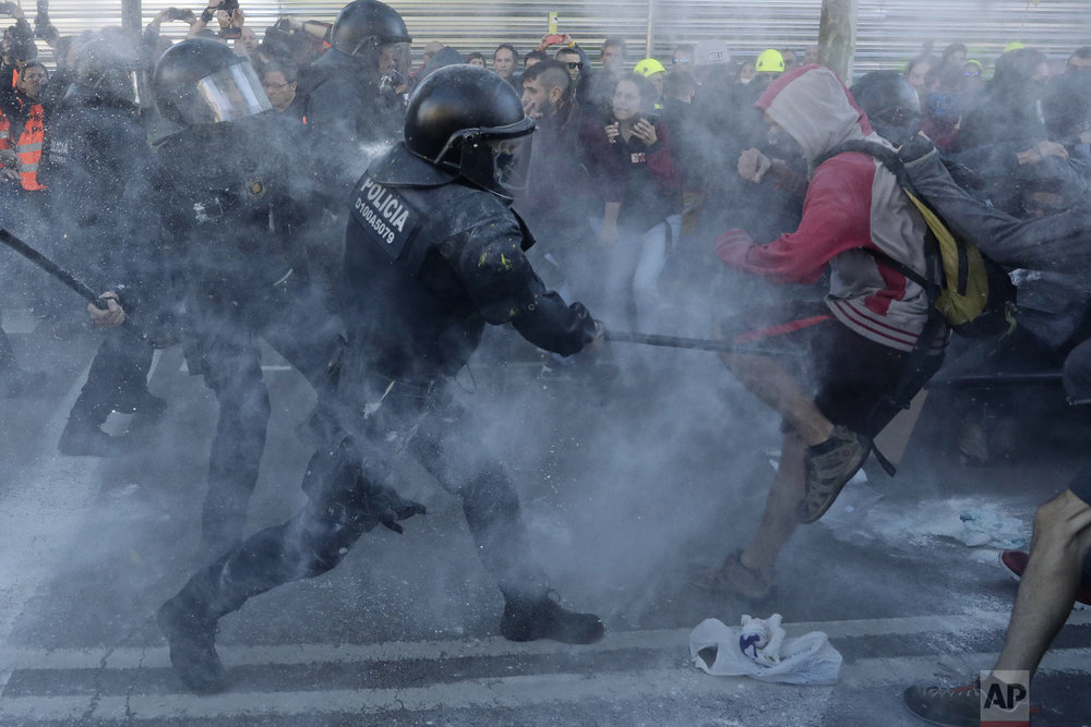 Police charge against protesters during a demonstration by CDR (Committees for the Defense of the Republic) in Barcelona, Spain, Saturday, Nov. 10, 2018. The CDR is a grassroots group that organizes protests in Catalonia to press their demand for independence. (AP Photo/Manu Fernandez)