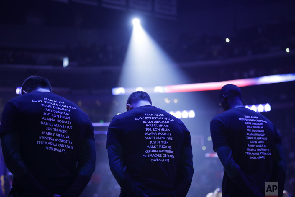 Players wear T-shirts bearing the names of the 12 victims killed in the shooting at a country bar in Thousand Oaks, Calif., as they listen to the national anthem before an NBA basketball game between the Los Angeles Clippers and the Milwaukee Bucks Saturday, Nov. 10, 2018, in Los Angeles. (AP Photo/Jae C. Hong)