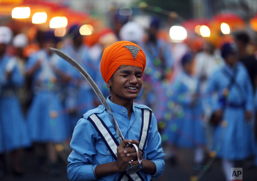 A Sikh boy reacts to a jovial comment from another as he prepares to display his martial art skills during a religious procession ahead of the birth anniversary of the first Sikh guru, Guru Nanak, Monday, Nov. 19, 2018, in Hyderabad, India. (AP Photo/Mahesh Kumar A.)