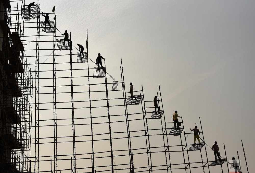 Indian laborers stand on scaffolding shift steel rods from the ground to the top of an under construction hospital building Thursday, Nov. 22, 2018, in Greater Noida, near New Delhi, India. (AP Photo/R S Iyer)