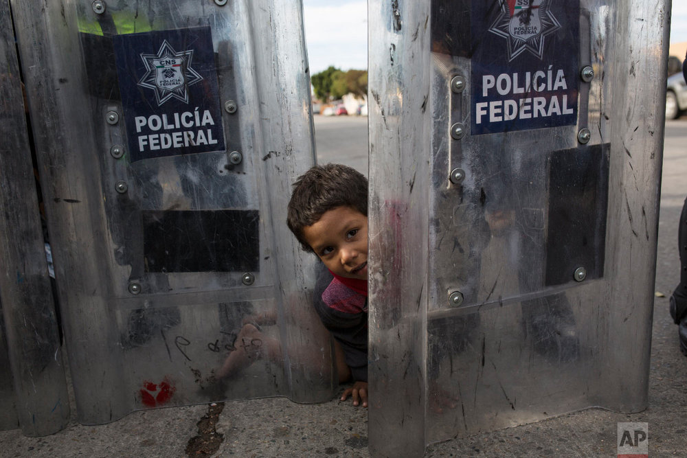 Elias Lopez, a three-year-old Honduran migrant, plays in between the shields of a line of Mexican riot police, when the group he was part of tried to cross the Chaparral border crossing in Tijuana, Mexico, Thursday, Nov. 22, 2018. (AP Photo/Rodrigo Abd)