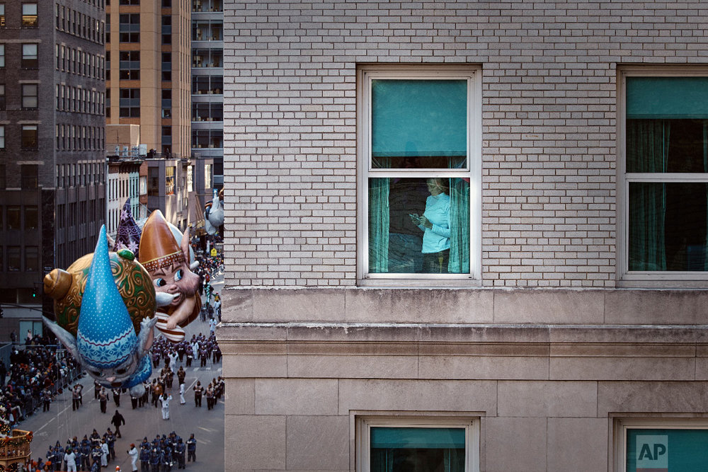 A woman checks her phone as balloons move through Sixth Avenue during the Macy's Thanksgiving Day Parade in New York, Thursday, Nov. 22, 2018. (AP Photo/Andres Kudacki)