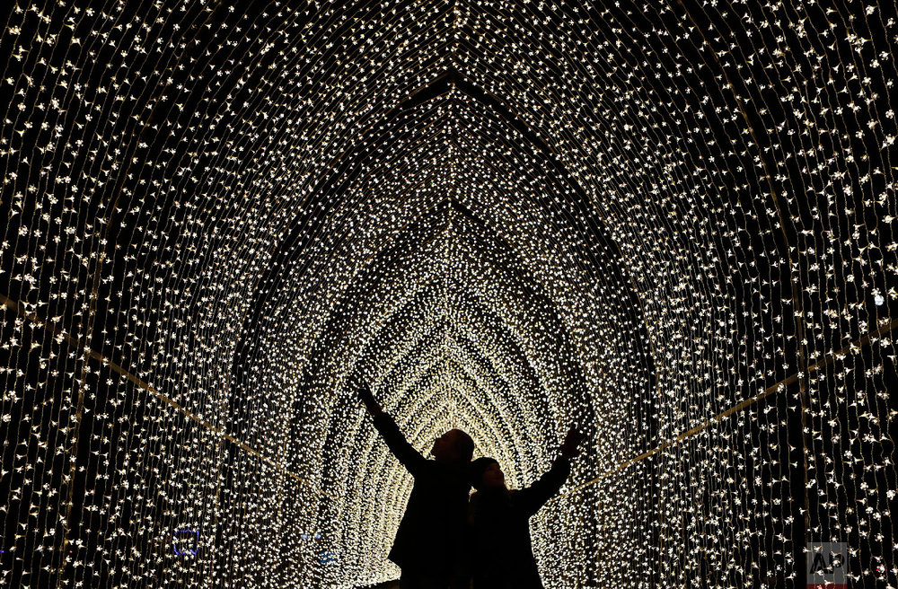 Children walk through the Cathedral of Light as part of the illuminated trail through Kew Gardens magnificent after-dark landscape, lit up by over one million twinkling lights in London, Wednesday, Nov. 21, 2018. (AP Photo/Frank Augstein)