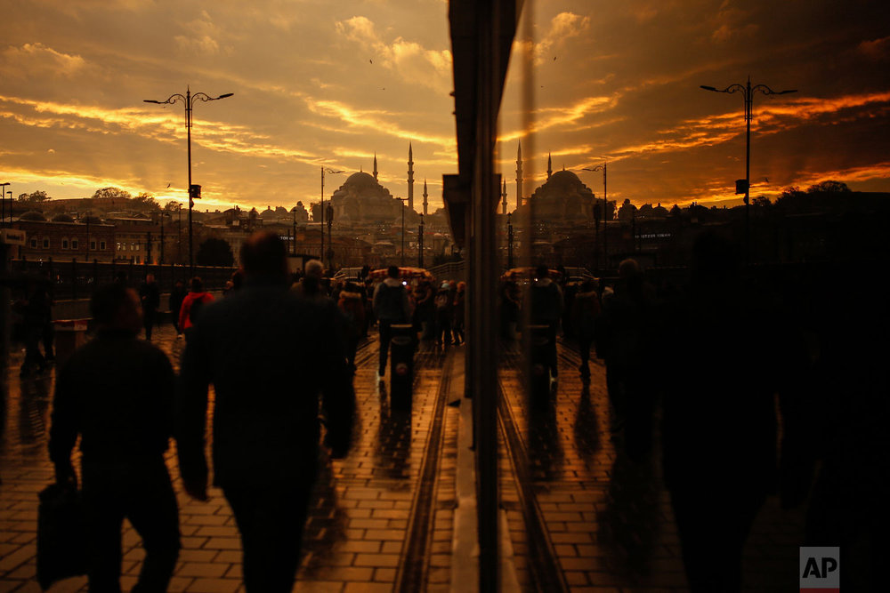 Backdropped by the iconic Suleymaniye Mosque in Istanbul, people are reflected in a glass as they walk on a bridge over the Golden Horn, Wednesday, Nov. 21, 2018. (AP Photo/Emrah Gurel)