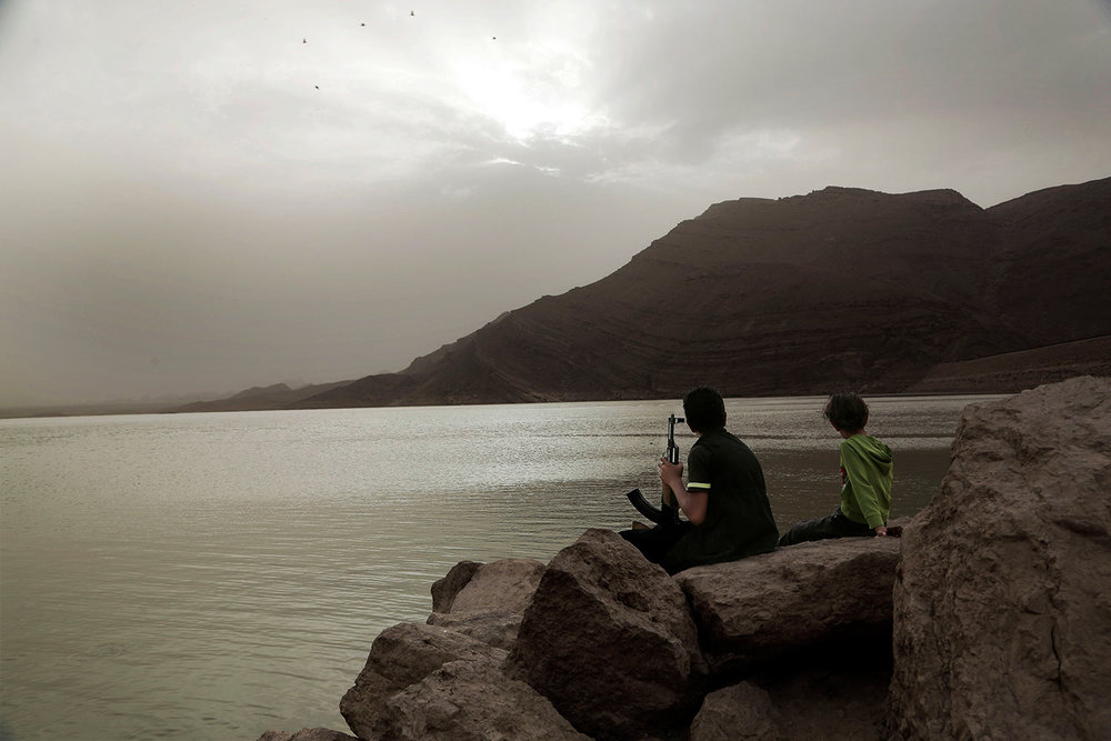 In this July 30, 2018, photo, a boy holds an AK-47 while overlooking the high dam in Marib, Yemen. (AP Photo/Nariman El-Mofty)