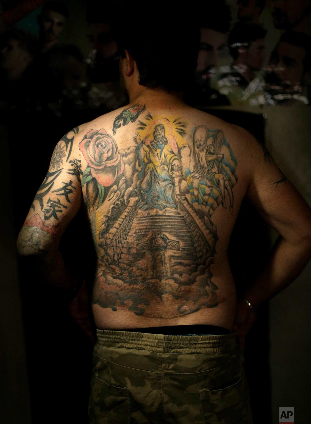 In this Wednesday. Oct. 24, 2018, Iraqi soldier Saad Khudeir displays tattoos on his body to cover scars of the burns he was injured in a car bomb, in Baghdad, Iraq. In 2008, Khudeir lost his fiancee and suffered burns on his body when a car bomb went off near his home in Sadr City, a district on the eastern side of the capital. Four years later, he endured burns in nearly 70 percent of his body when a suicide bomber rammed his explosives-laden car into his convoy in the then restive city of Fallujah. (AP Photo/Hadi Mizban)