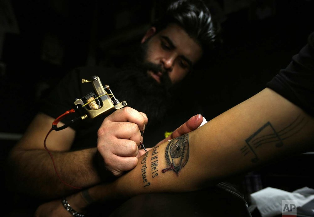 In this Tuesday. Oct. 23, 2018, photo, a man gets a tattoo on his arm in a tattoo studio in Baghdad, Iraq. One tattoo shop owner said he receives an average of 20 persons a year who want to cover their scars with tattoos, a nearly 30 percent increase from last year. (AP Photo/Hadi Mizban)