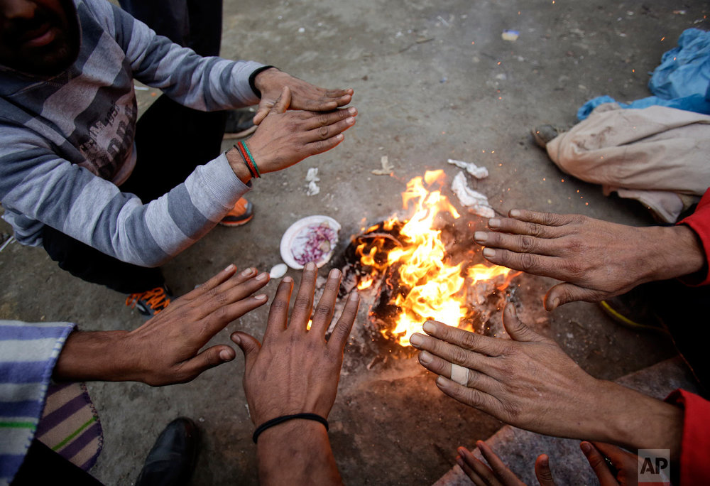 Migrants warm their hands above a fire at a camp in Velika Kladusa, Bosnia, close to the border to Croatia, Sunday, Nov. 18, 2018. (AP Photo/Amel Emric)