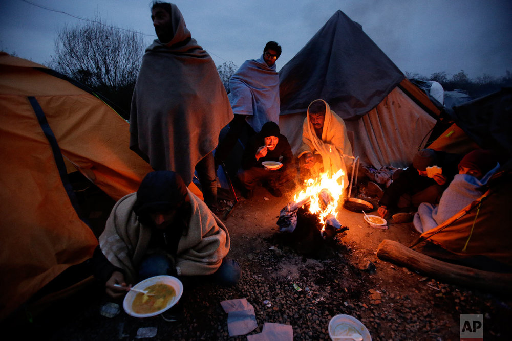 Migrants eat around a fire at a camp in Velika Kladusa, Bosnia, close to the border to Croatia, Sunday, Nov. 18, 2018. (AP Photo/Amel Emric)