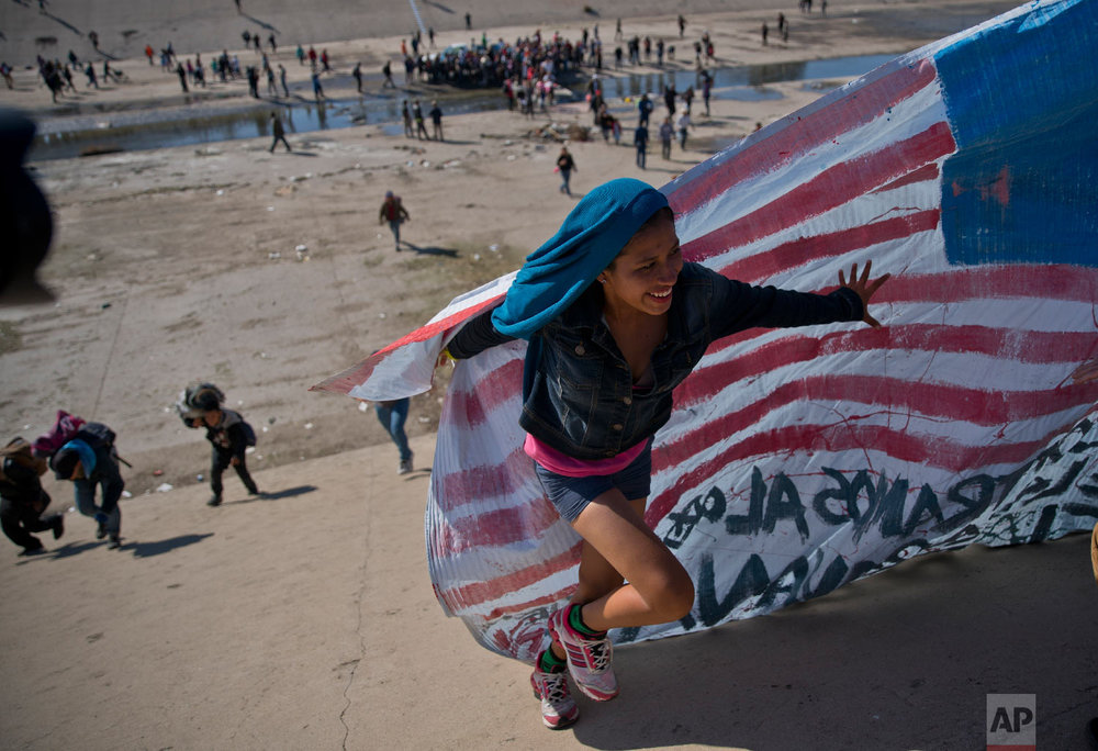 A migrant woman helps carry a handmade U.S. flag up the riverbank at the Mexico-U.S. border after getting past Mexican police at the Chaparral border crossing in Tijuana, Mexico, Sunday, Nov. 25, 2018, as a group of migrants tries to reach the U.S.  (AP Photo/Ramon Espinosa)