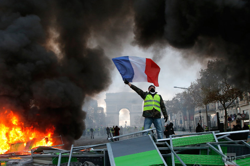 A demonstrator waves the French flag onto a burning barricade on the Champs-Elysees avenue with the Arc de Triomphe in background, during a demonstration against the rise of fuel taxes, Saturday, Nov. 24, 2018 in Paris. (AP Photo/Michel Euler)