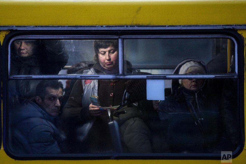 People ride a bus in Mariupol, south coast of Azov sea, eastern Ukraine, Friday, Nov. 30, 2018. (AP Photo/Evgeniy Maloletka)