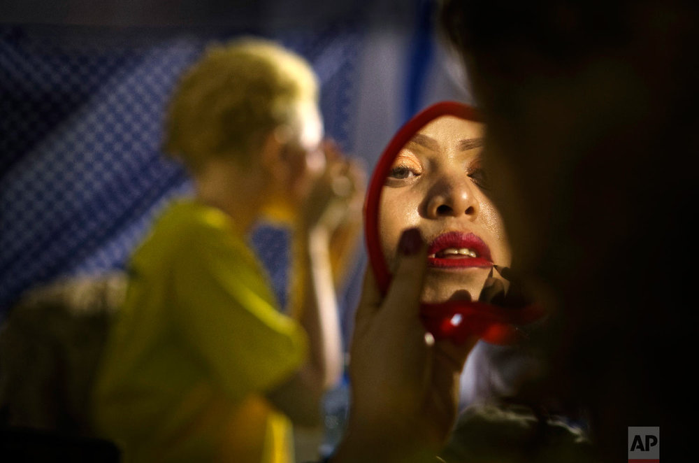 A contestant checks her makeup in a mirror as she prepares to perform in the Mr. & Miss Albinism East Africa contest, organized by the Albinism Society of Kenya, in Nairobi, Kenya, Nov. 30, 2018. (AP Photo/Ben Curtis)