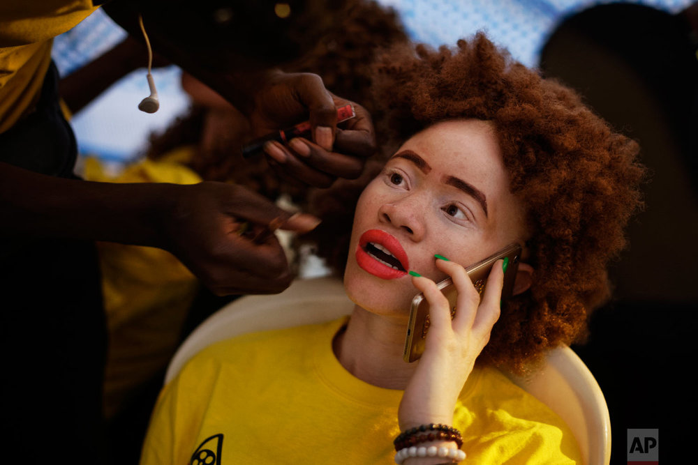 "A contestant talks on her mobile phone while having her makeup done as she prepares to perform in the ""Mr. & Miss Albinism East Africa"" contest, organized by the Albinism Society of Kenya, in Nairobi, Kenya, Nov. 30, 2018. (AP Photo/Ben Curtis)"