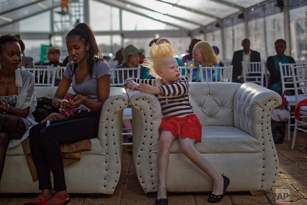 Albino girl Rebecca Zawadi, 8, right, sits next to Marion Jacklin, center-left, who helps train the contestants, as they wait for the start of the Mr. & Miss Albinism East Afric contest, organized by the Albinism Society of Kenya, in Nairobi, Kenya, Nov. 30, 2018. (AP Photo/Ben Curtis)