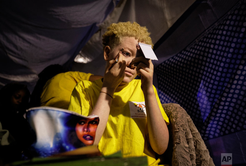 Kenyan contestant Lucianah Nyawira, 21, does her makeup as she prepares to perform in the Mr. & Miss Albinism East Africa contest, organized by the Albinism Society of Kenya, in Nairobi, Kenya, Nov. 30, 2018. (AP Photo/Ben Curtis)