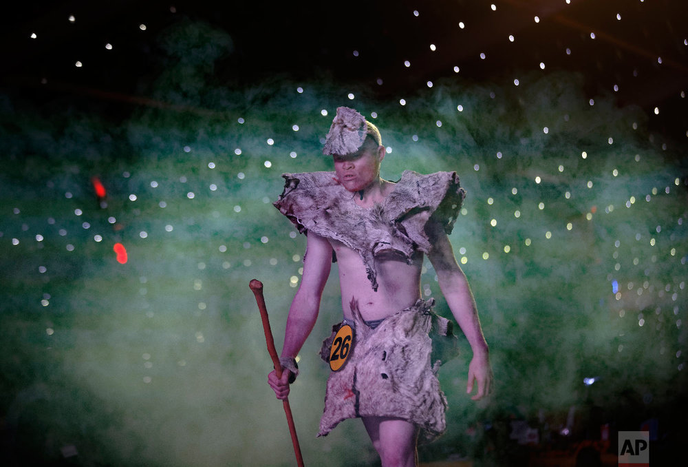 A contestant wearing a traditional costume of animal hides performs in the Mr. & Miss Albinism East Africa contest, organized by the Albinism Society of Kenya, in Nairobi, Kenya, Nov. 30, 2018. (AP Photo/Ben Curtis)