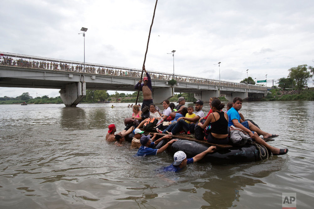 A group of Central American migrants cross the Suchiate River aboard a raft made out of tractor inner tubes and wooden planks, on the the border between Guatemala and Mexico, in Ciudad Hidalgo, Mexico, Oct. 20, 2018. (AP Photo/Moises Castillo)
