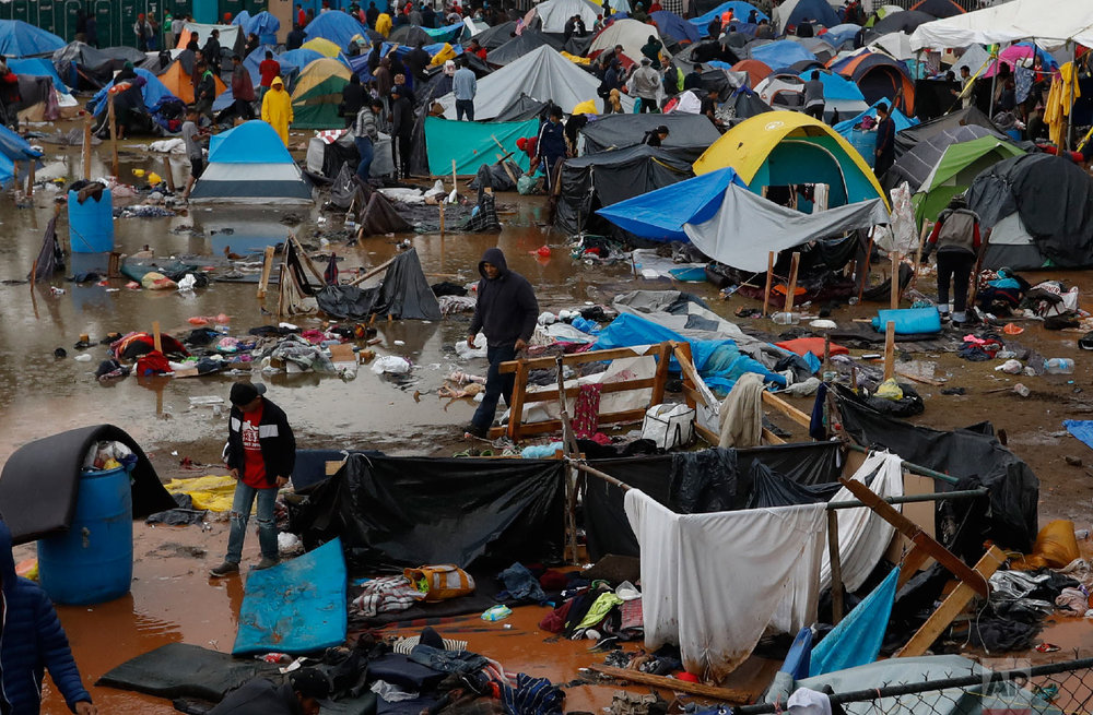Migrants walk amidst flooded tents after heavy rains poured down on a sports complex sheltering thousands of Central Americans in Tijuana, Mexico, on Nov. 29, 2018. (AP Photo/Rebecca Blackwell)
