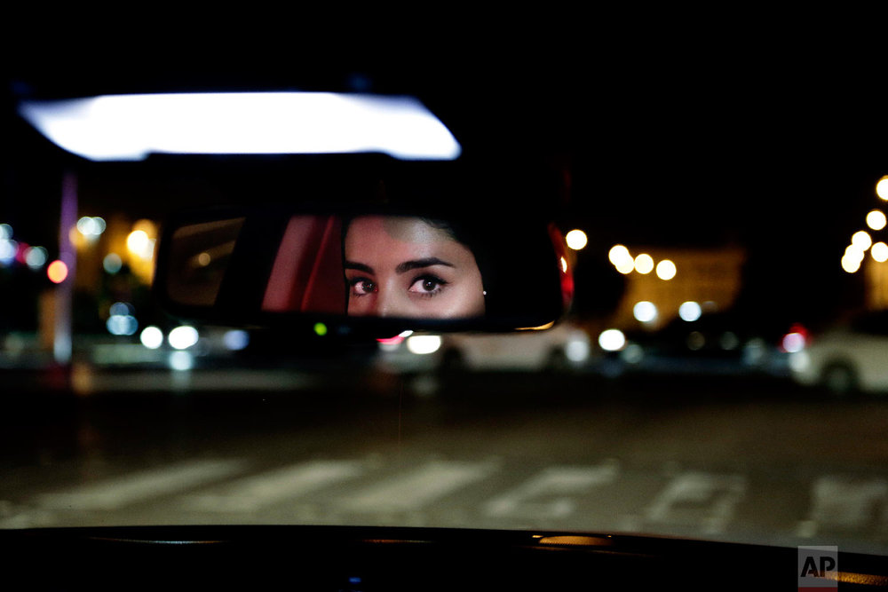 Hessah al-Ajaji drives her car down busy Tahlia Street after midnight for the first time in Saudi Arabia's capital Riyadh on June 24, 2018, just minutes after the world's last remaining ban on women driving was lifted. (AP Photo/Nariman El-Mofty)