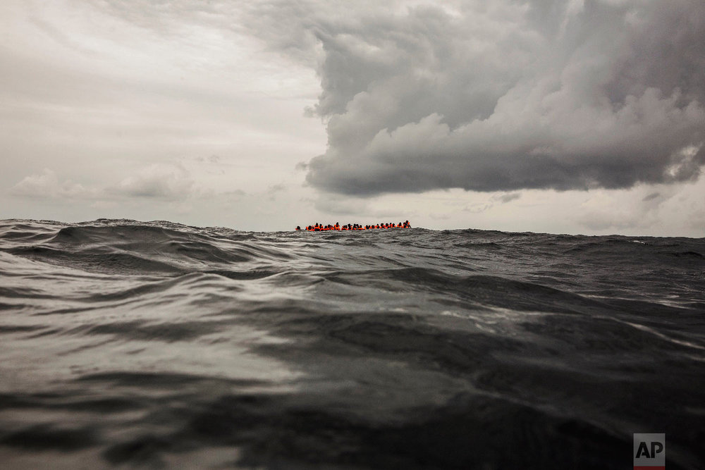 Refugees and migrants wait to be rescued by aid workers from the Spanish NGO Proactiva Open Arms, 60 miles north of Al-Khums, Libya, on Feb. 18, 2018, after leaving Libya aboard an overcrowded rubber boat in an attempt to reach European soil. (AP Photo/Olmo Calvo)