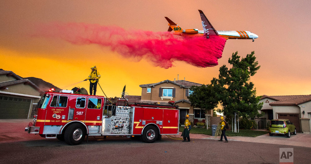 A plane drops fire retardant behind homes along McVicker Canyon Park Road in Lake Elsinore, Calif., as the Holy Fire burned near homes on Aug. 8, 2018. (Mark Rightmire/The Orange County Register via AP)