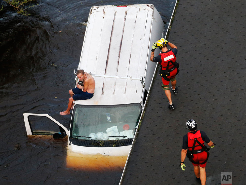 U.S. Coast Guard rescue swimmers Samuel Knoeppel, center, and Randy Haba, bottom right, approach Willie Schubert on a stranded van in Pollocksville, N.C., on Sept. 17, 2018, in the aftermath of Hurricane Florence. (AP Photo/Steve Helber)