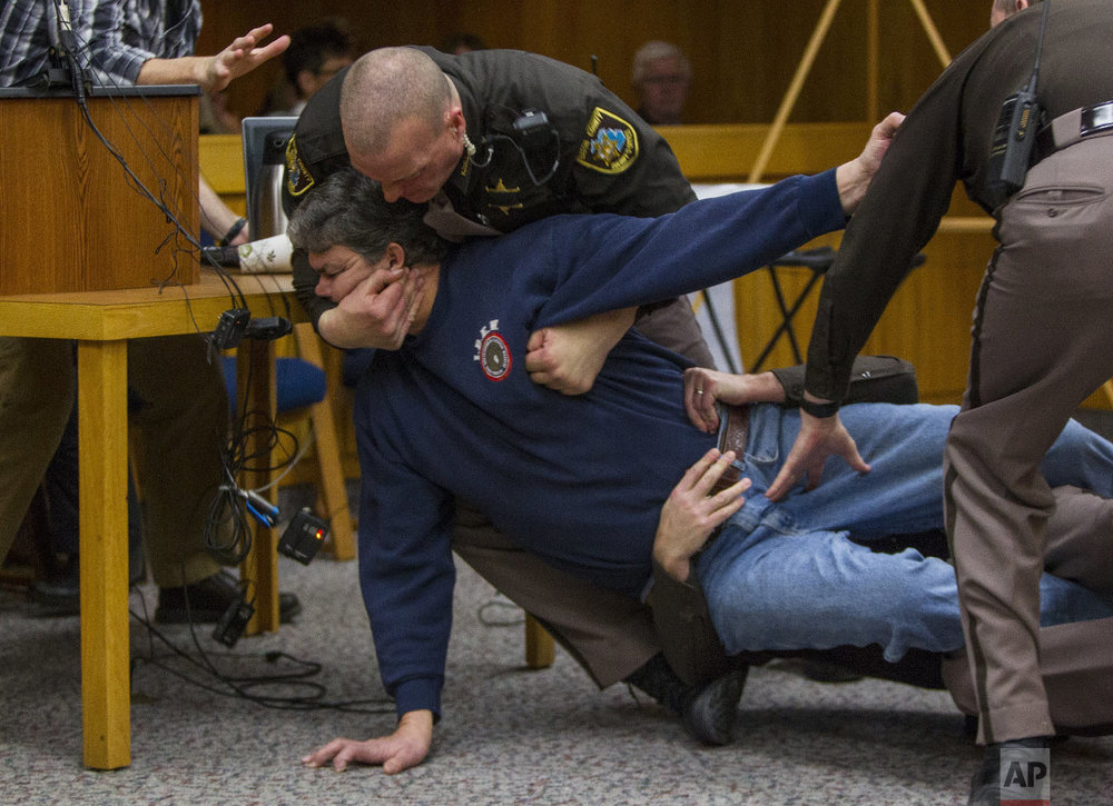 Eaton County Sheriff's deputies restrain Randall Margraves, father of three victims of Larry Nassar, on Feb. 2, 2018, in Eaton County Circuit Court in Charlotte, Mich. The incident came during the third and final sentencing hearing for Nassar on sexual abuse charges. (Cory Morse/The Grand Rapids Press via AP)