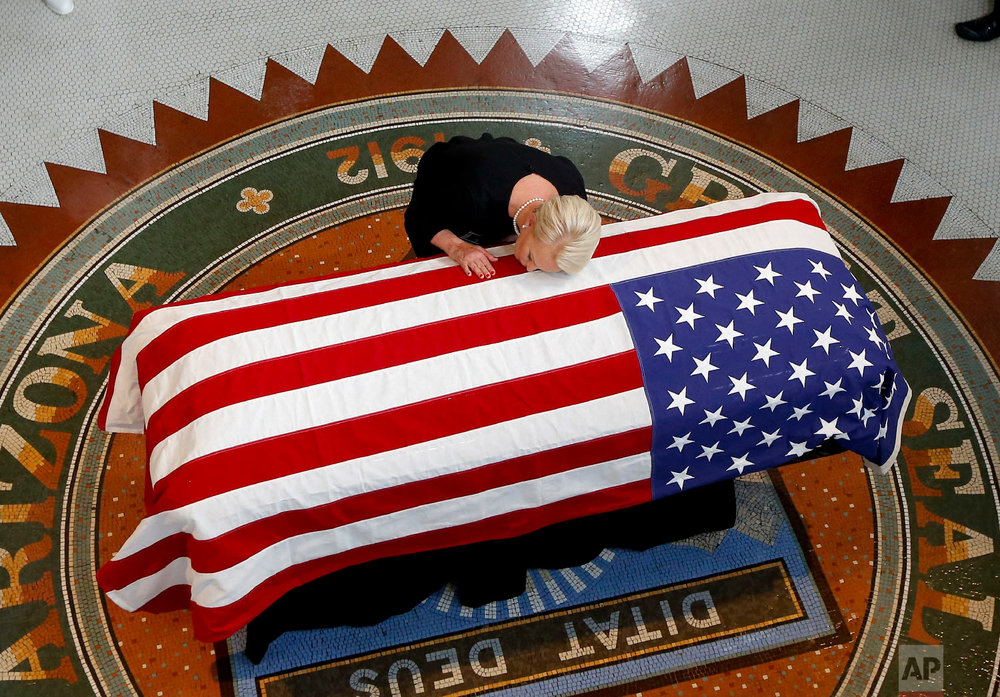 Cindy McCain, wife of Sen. John McCain, R-Ariz., rests her head on his casket during a memorial service at the Arizona Capitol in Phoenix on Aug. 29, 2018. (AP Photo/Ross D. Franklin)