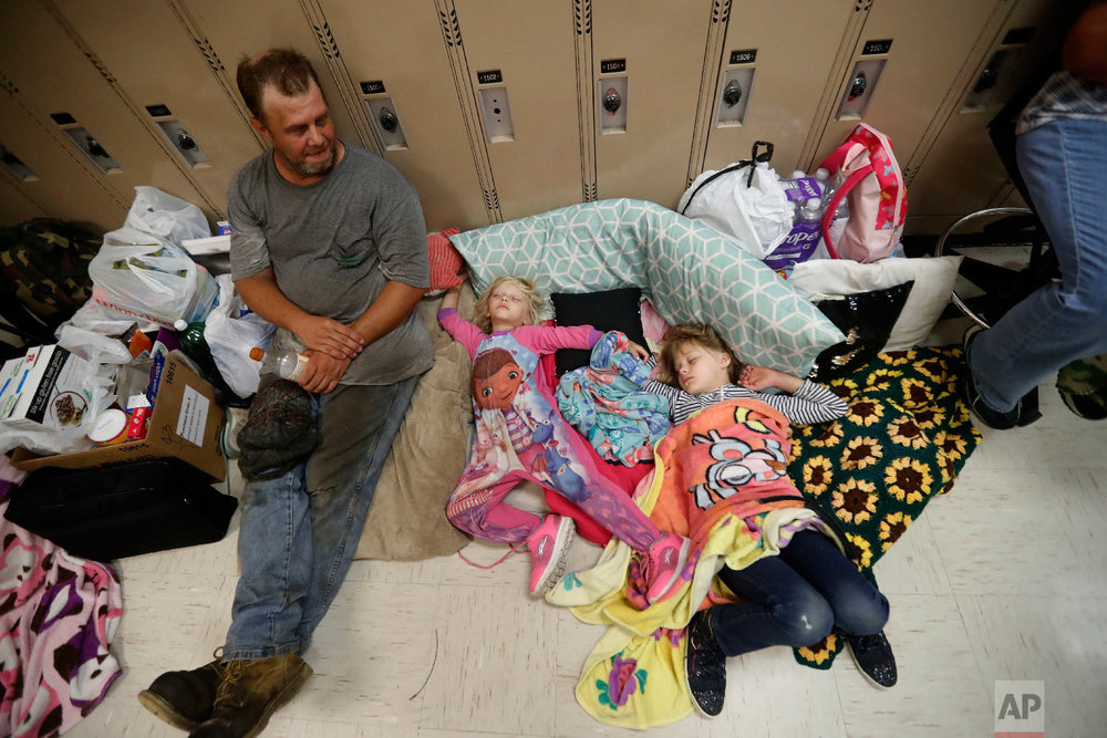 Earnest Sweet sits while his daughters Terri, 4, center, and Anna, 7, sleep at an evacuation shelter set up at Rutherford High School in Panama City Beach, Fla., in advance of Hurricane Michael, which is expected to make landfall on Oct. 10, 2018. (AP Photo/Gerald Herbert)