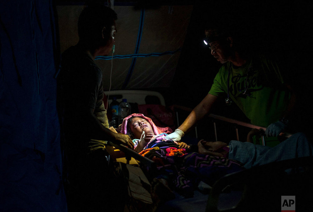 A doctor examines children at a makeshift hospital in Tanjung, Indonesia, on Lombok Island, on Aug. 6, 2018, a day after a powerful earthquake flattened houses and toppled bridges on the Indonesian tourist island. (AP Photo/Fauzy Chaniago)
