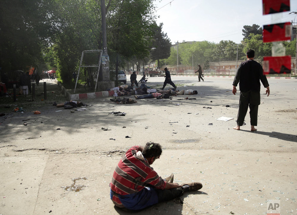 A wounded man sits on the ground after explosions in central Kabul, Afghanistan, on April 30, 2018, following a coordinated double suicide bombing. (AP Photo/Massoud Hossaini)