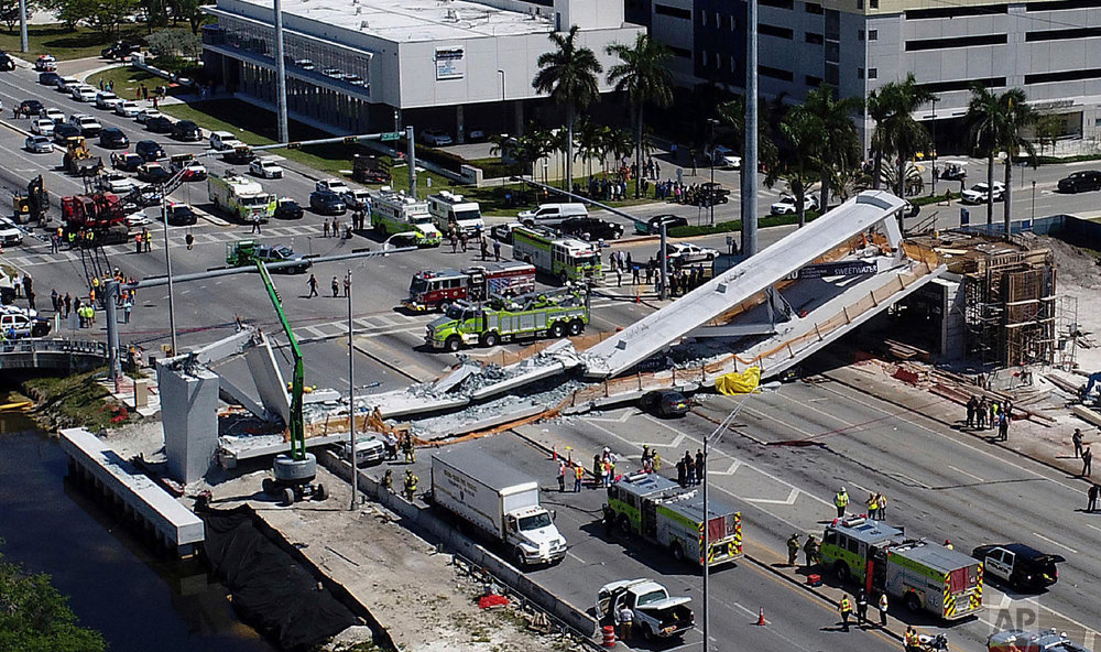 Emergency personnel respond after a brand-new pedestrian bridge collapsed onto a highway at Florida International University in Miami, crushing cars and killing several people, on March 15, 2018. (Pedro Portal/Miami Herald via AP)