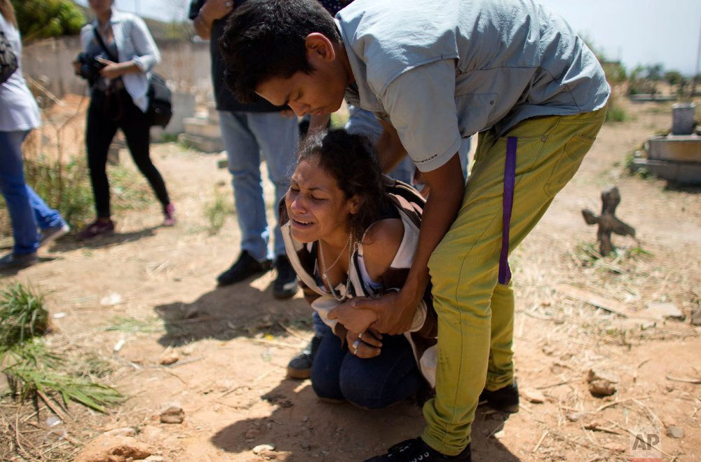 A woman grieves during the funeral of Alirio Duran, 25, at the Municipal Cemetery of Valencia, Venezuela, on March 30, 2018. Duran was one of 68 victims who were killed in a police station fire. (AP Photo/Ariana Cubillos)