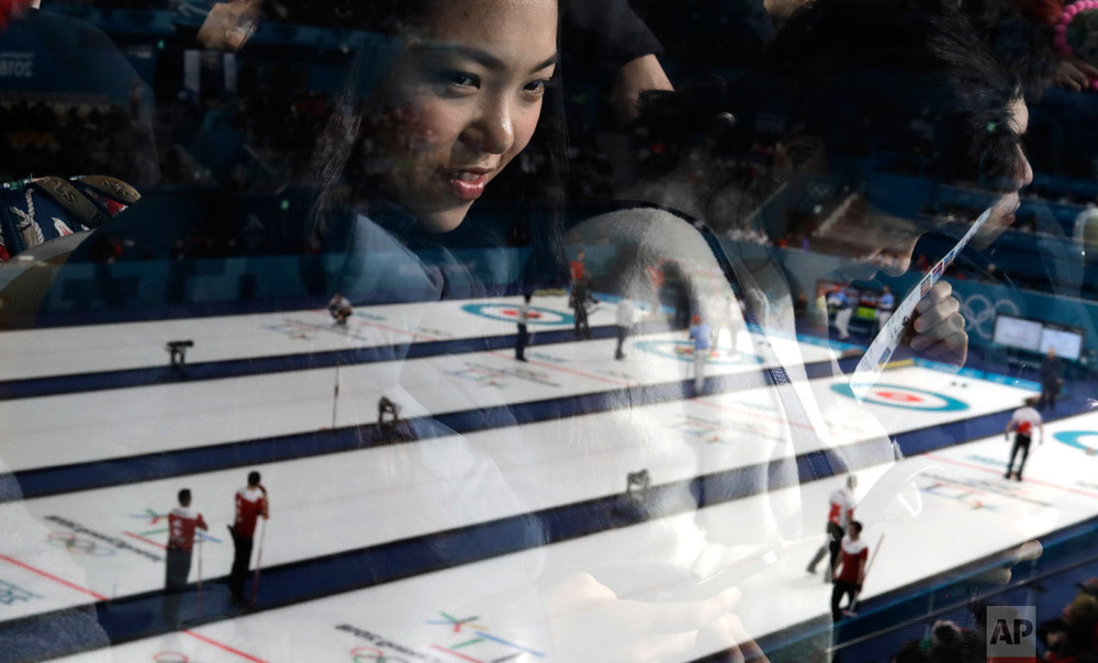 A woman's face is reflected in glass as she watches men's curling matches at the 2018 Winter Olympics in Gangneung, South Korea, on Feb. 18, 2018. (AP Photo/Natacha Pisarenko)