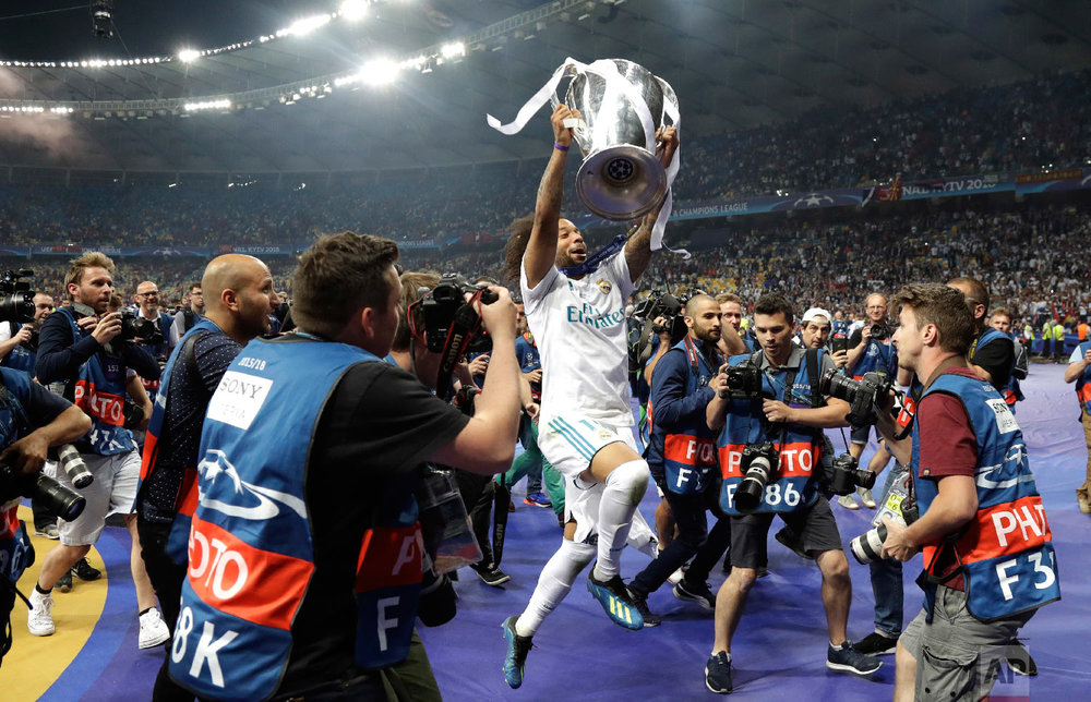 Real Madrid's Marcelo celebrates with the trophy after winning the Champions League Final soccer match against Liverpool at the Olimpiyskiy Stadium in Kiev, Ukraine, on May 26, 2018. (AP Photo/Matthias Schrader)
