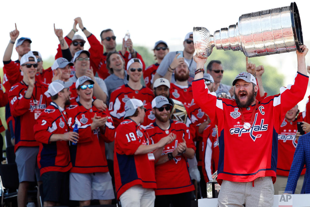 Washington Capitals Alex Ovechkin, of Russia, holds the Stanley Cup aloft during a victory rally on the National Mall in Washington on June 12, 2018. This was the first championship title for the Washington Capitals. (AP Photo/Jacquelyn Martin)