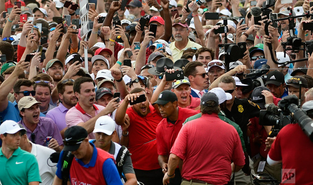 Tiger Woods, lower center, and Rory McIlroy, lower left, emerge from a horde of fans following Tiger on their way to the 18th green during the final round of the Tour Championship golf tournament in Atlanta on Sept. 23, 2018. (AP Photo/John Amis)