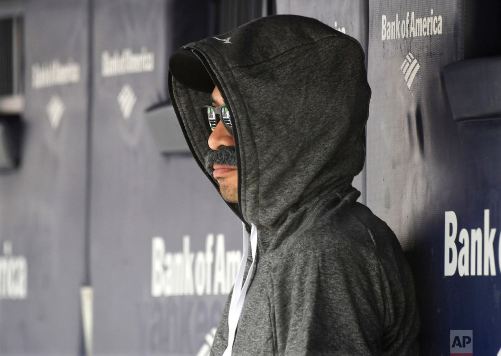 Ichiro Suzuki, special assistant to the chairman of the Seattle Mariners, sits in the dugout disguised with a fake mustache and a hoodie as he watches the New York Yankees bat during the first inning of a baseball game on June 21, 2018, at Yankee Stadium in New York. (AP Photo/Bill Kostroun)