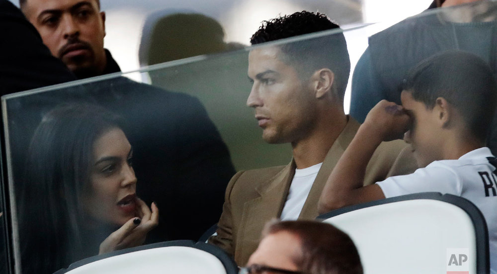 Juventus forward Cristiano Ronaldo, center, is flanked by his girlfriend Georgina, left, and his son Cristiano Jr., as he sits in the stands during a Champions League group H soccer match between Juventus and Young Boys, at the Allianz stadium in Turin, Italy, on Oct. 2, 2018. (AP Photo/Luca Bruno)