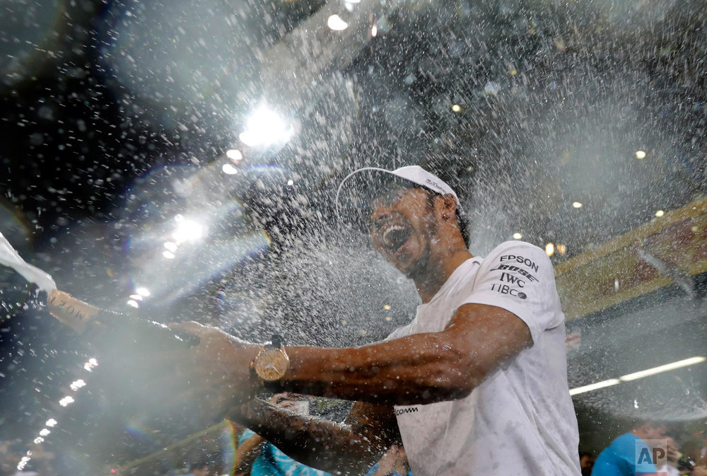 Mercedes driver Lewis Hamilton, of Britain, sprays champagne after winning the Emirates Formula One Grand Prix at the Yas Marina racetrack in Abu Dhabi, United Arab Emirates, on Nov. 25, 2018. (AP Photo/Hassan Ammar)