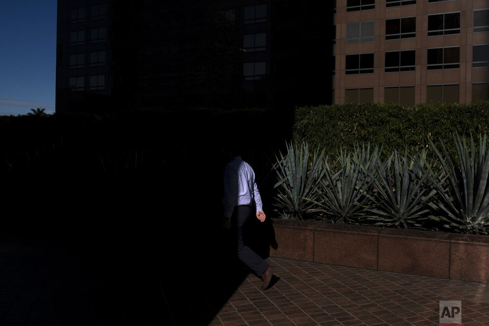 A pedestrian walks into the shadow cast by a building Tuesday, Dec. 4, 2018, in downtown Los Angeles. (AP Photo/Jae C. Hong)