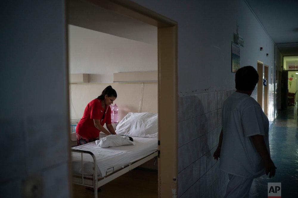 A nurse walks past a room as Paulina Balazova swaddles her newborn baby at a hospital on Nov. 15, 2018, in Trebisov, Slovakia. (AP Photo/Felipe Dana)