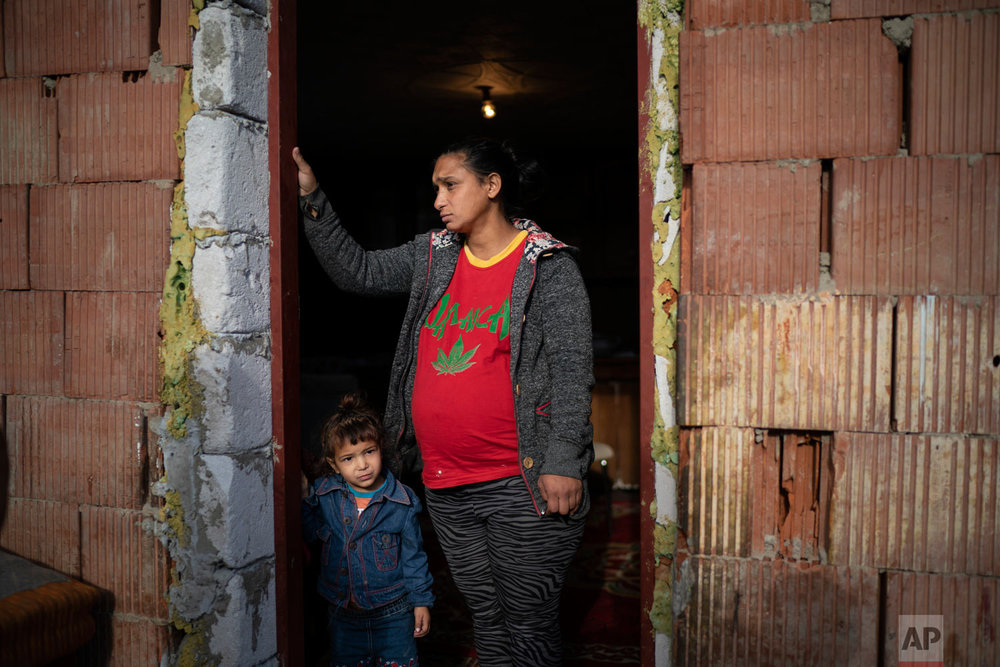 Jarmila Noskova, 33, stands at the entrance of her house with her daughter on Nov. 14, 2018, in Podhorany village near Kezmarok, Slovakia. Noskova, a Roma woman now pregnant with her seventh child, said she cried for days every time she was forced to remain in the hospital after birth, terrified the hospital would alert the police if she left. (AP Photo/Felipe Dana)