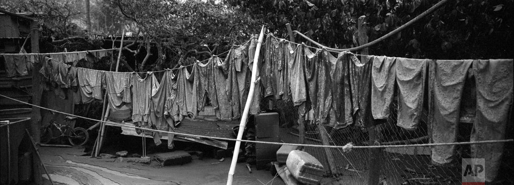 """Apparel hung on a clothesline are covered in volcanic ash outside a home in the disaster zone near the Volcan de Fuego, or """"Volcano of Fire, on June 6 in San Miguel Los Lotes, Escuintla, Guatemala. (AP Photo/Rodrigo Abd)"""
