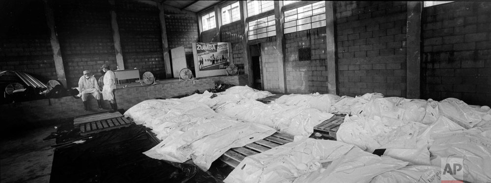 A forensic worker stands while another rests next to body bags containing the remains of victims of the Volcan de Fuego, or Volcano of Fire, eruption, in a cinderblock warehouse converted into a makeshift morgue on June 8, 2018, in Escuintla, Guatemala. (AP Photo/Rodrigo Abd)