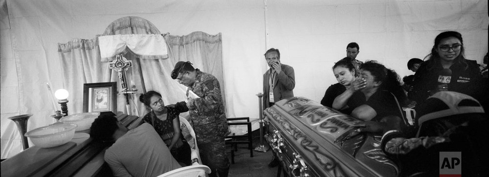A military chaplain reads the Bible to Francisca Nij and her brother Francisco during the wake for their mother Maritza Nij Ramos Davila, 40, on June 7, 2018, in Alotenango, Guatemala. (AP Photo/Rodrigo Abd)