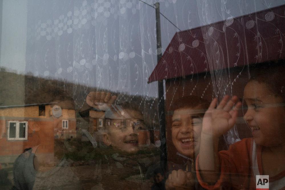 Homes are reflected off the window of Monika Krcova's house as her grandchildren play inside at the Podhorany village on Nov. 14, 2018, near Kezmarok, Slovakia. (AP Photo/Felipe Dana)